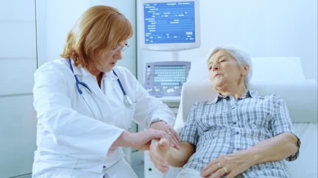 Female doctor checking the senior womans pulse on the wrist