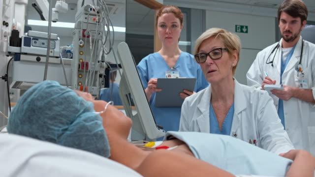"""vidéos et rushes de ds femme médecin vérifiant sur femme allongée dans l """" unité de soins intensifs - vêtements professionnels hospitaliers"""