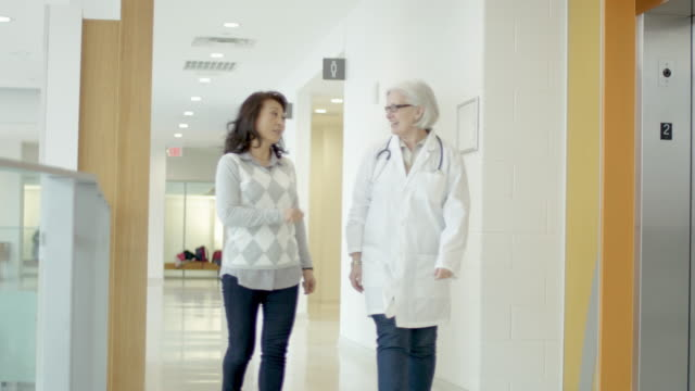 female doctor consulting with her ethnic senior female patient - fatcamera stock videos and b-roll footage