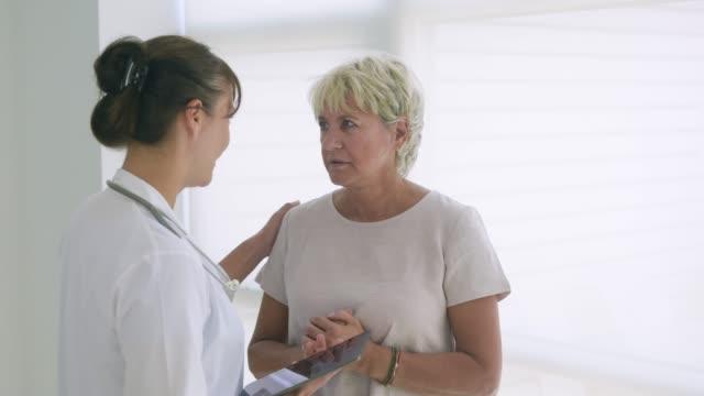 vidéos et rushes de female doctor delivering good news to mature woman. - bonne nouvelle