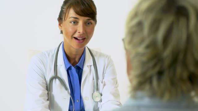 female doctor delivering good news to mature woman. - hand aufs herz stock-videos und b-roll-filmmaterial