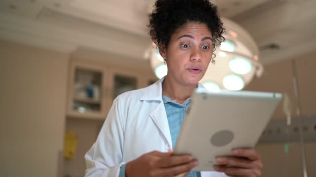 female doctor doing a video call using digital tablet at hospital - remote location stock videos & royalty-free footage