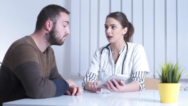 vidéos et rushes de docteur féminin expliquant des issues de santé sur le comprimé à un patient - mauvaise nouvelle