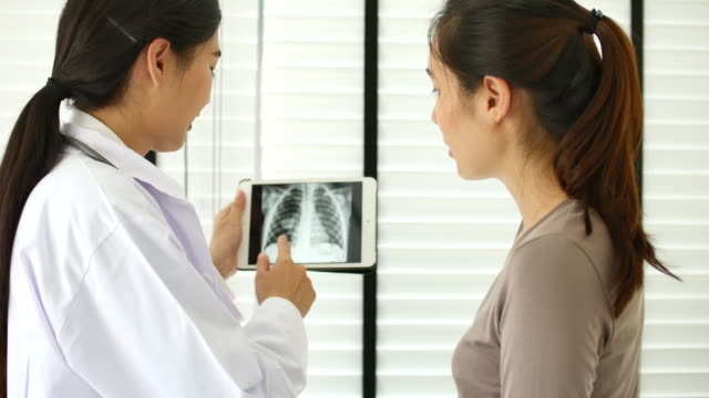 Female doctor explaining something with her patient on tablet computer