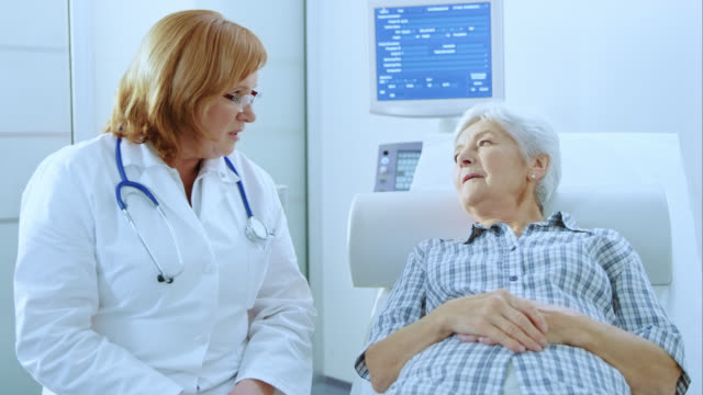 female doctor explaining to senior woman that she is ok - blonde hair stock videos & royalty-free footage