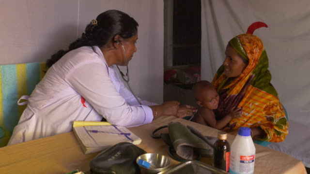 A female Doctor from an NGO in rural Bangladesh examines a baby boy and discusses healthcare with the mother