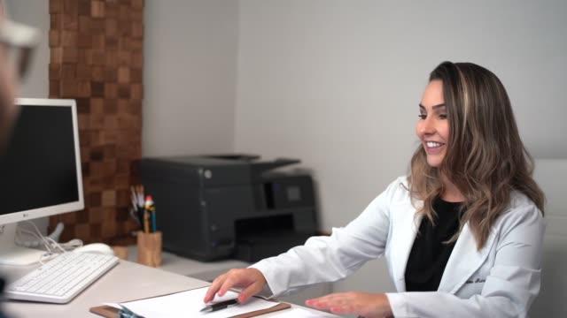 vídeos de stock, filmes e b-roll de doutor fêmea que dá uma medicina da prescrição - dentista