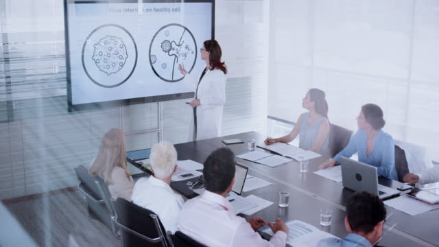 Female doctor giving a presentation on a virus to her colleagues in the conference room