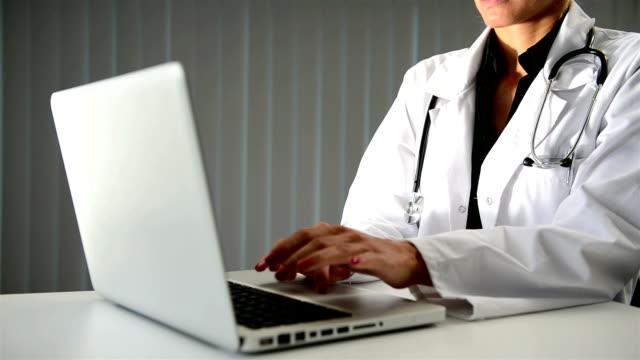 Weiblich Arzt hand Tippen auf laptop