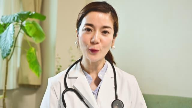 女性医師はフロントカメラでビデオ会議を開催しています。 - 離れた点の映像素材/bロール
