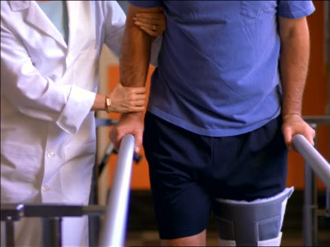 female doctor helping middle-aged male patient with leg brace walk slowly in physical therapy - recovery stock videos & royalty-free footage