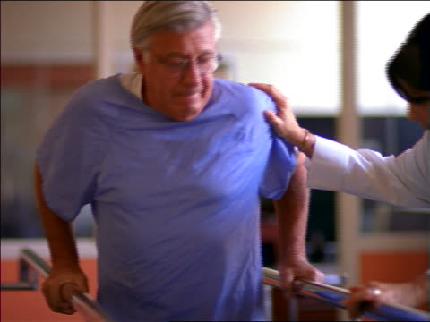 Female doctor helping senior male patient in hospital gown walk in rehab / physical therapy