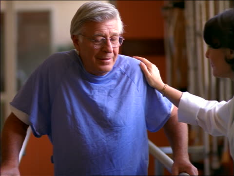 Female doctor helping senior male patient in hospital gown walk slowly in rehab / physical therapy
