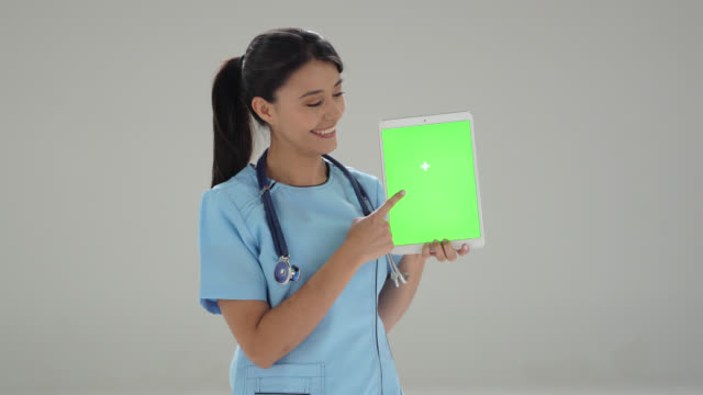female doctor holding a tablet pointing at editable screen - chroma key - pointing stock videos & royalty-free footage