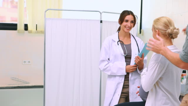 Female doctor holding files while talking to a pregnant woman and her husband