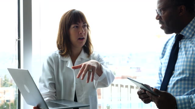 ms female doctor holding laptop discussing patient information with colleague in exam room - タータンチェック点の映像素材/bロール