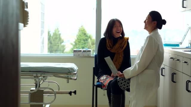 vídeos y material grabado en eventos de stock de ms female doctor in discussion with senior female patient in exam room - toma mediana