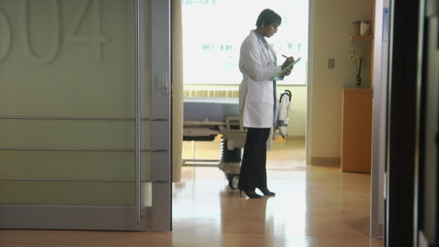 WS Female doctor in empty hospital room with clipboard, smiling at camera, Seattle, Washington, USA
