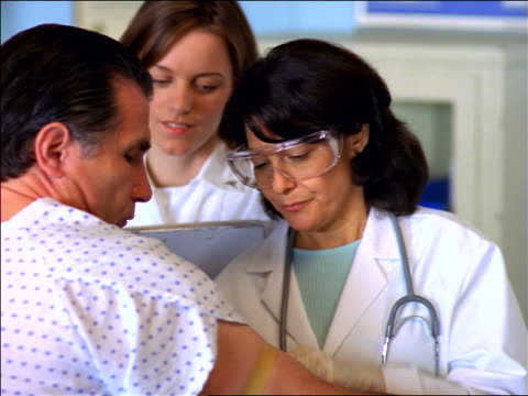 Female doctor in goggles preparing middle-aged male patient's arm for blood test / nurse in background