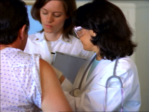 vidéos et rushes de female doctor in goggles preparing middle-aged male patient's arm for injection / nurse in background - homme dans un groupe de femmes