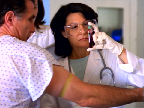 female doctor in goggles with middle-aged male patient holding up vial of blood + handing it to nurse - maschio con gruppo di femmine video stock e b–roll