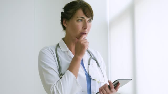 female doctor in office working with digital tablet. - camice da medico video stock e b–roll