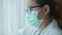 Female doctor in surgical mask looking out the window,Close-up