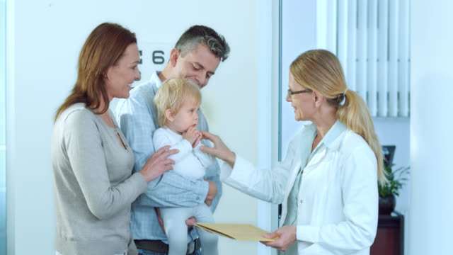 Female doctor keeping little girl busy when talking to parents