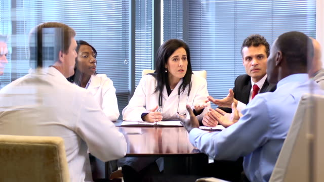 female doctor leads a meeting with professionals - ws - pointer stock videos & royalty-free footage