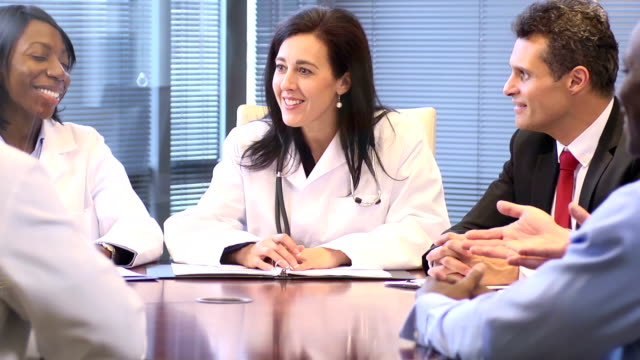 female doctor leads a meeting with professionals - cu - medical leadership stock videos & royalty-free footage