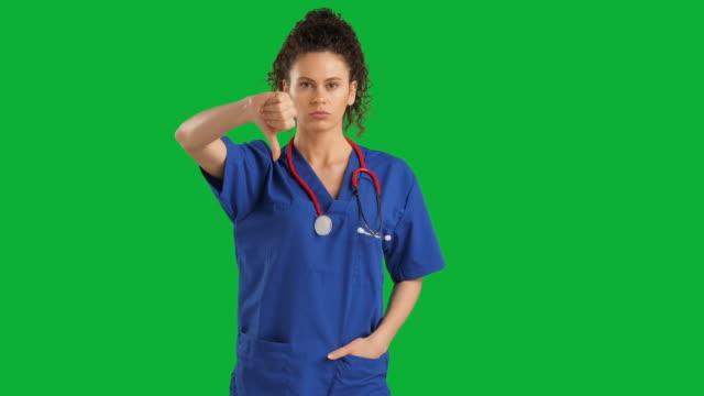 vidéos et rushes de docteur féminin regardant l'appareil-photo sur le fond vert d'écran de clef de chroma, l'émotion négative - touche de couleur