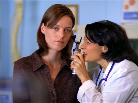 Female doctor looking in female patient's ear with otoscope