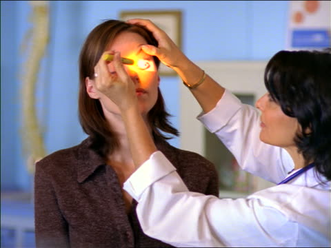 stockvideo's en b-roll-footage met female doctor looking in female patient's eyes with flashlight - opticien