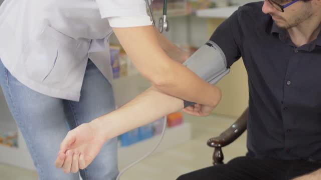 stockvideo's en b-roll-footage met de vrouwelijke arts meet druk in een kliniek met krullend behaarde jonge mensen - zorgzaamheid