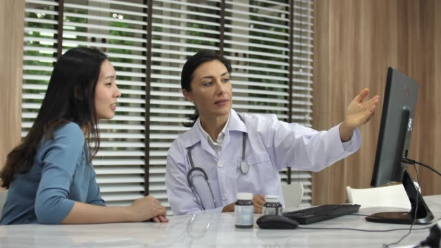 female doctor meets with asian patient in office - good news stock videos & royalty-free footage