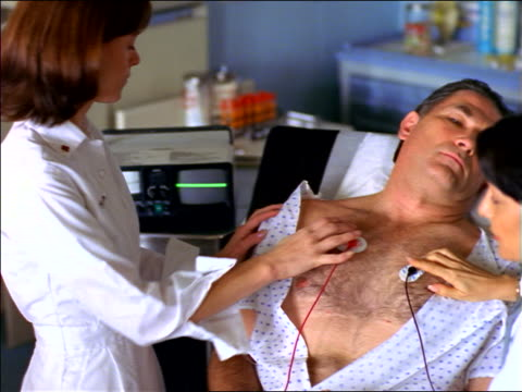 female doctor + nurse attaching electrodes to chest of middle-aged patient in hospital - maschio con gruppo di femmine video stock e b–roll