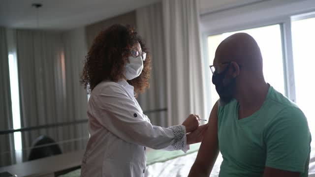 female doctor or nurse vaccinating a man at home - wearing face mask - epidemiology stock videos & royalty-free footage