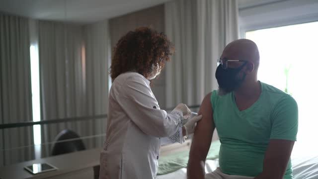 stockvideo's en b-roll-footage met vrouwelijke arts of verpleegster die een mens thuis vaccineert - die gezichtsmasker draagt - buiten de vs