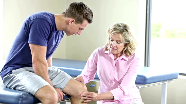 Female doctor or physical therapist examining patient's knee