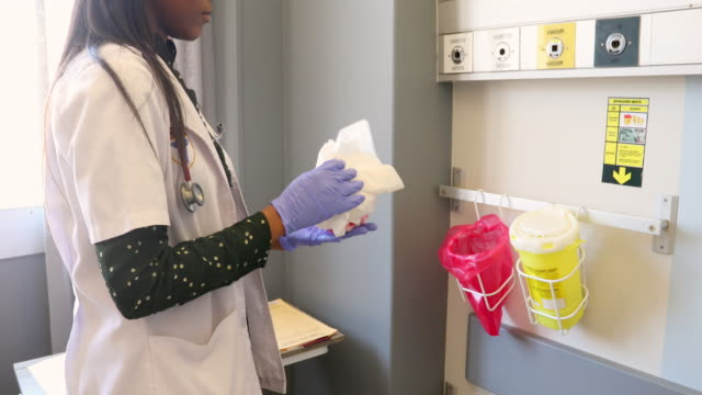 female doctor properly disposing of medical waste in a hospital - waste management stock videos & royalty-free footage
