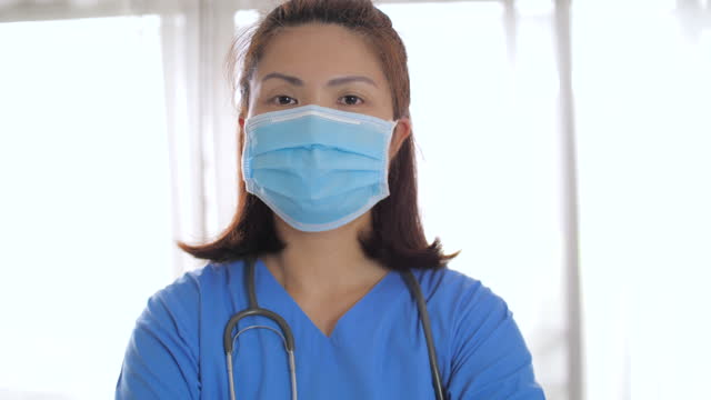 female doctor puts on a face a medical mask - female doctor stock videos & royalty-free footage