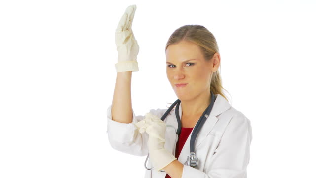 vídeos de stock, filmes e b-roll de female doctor putting on gloves - luvas