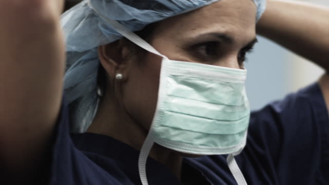 stockvideo's en b-roll-footage met cu female doctor putting on surgical mask / payson, utah, usa - chirurg