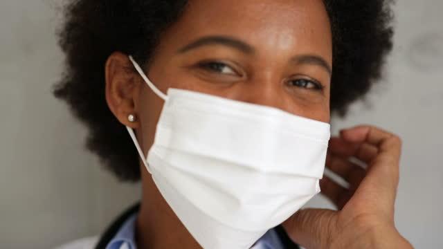 vídeos de stock, filmes e b-roll de médica removendo a máscara e olhando na câmera com sorriso - taking off