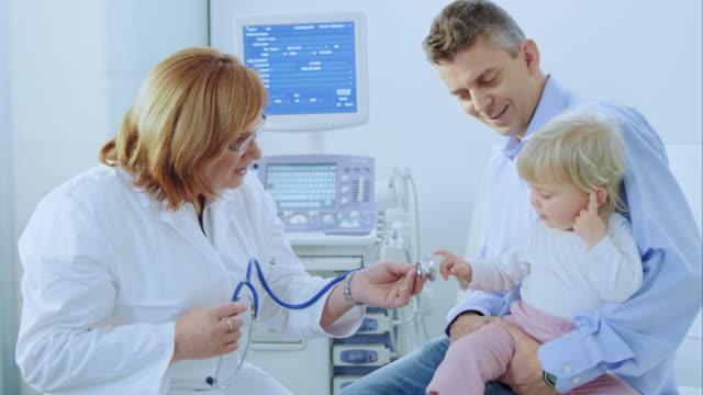 Ärztin mit Stethoskop auscultating für Kleinkinder die vor