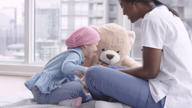 vídeos y material grabado en eventos de stock de la doctora se sienta con un niño paciente que lucha contra el cáncer - enfermedad