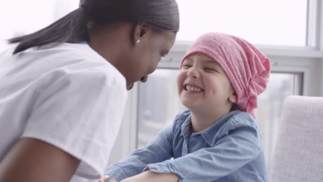 female doctor sits with child patient fighting cancer - patient stock videos & royalty-free footage