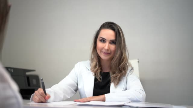 female doctor sitting at desk in clinic - clinic stock videos & royalty-free footage