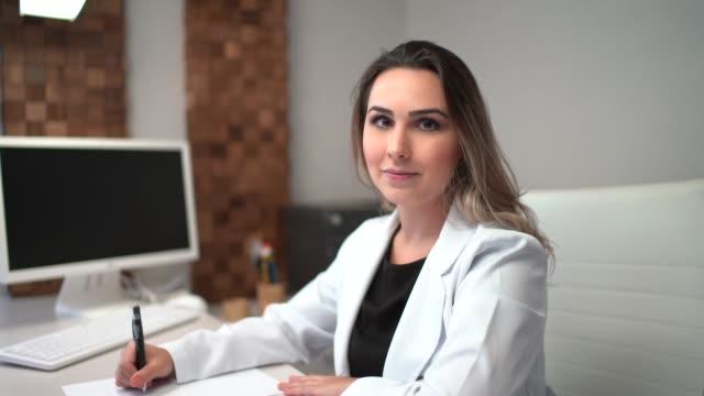 vídeos y material grabado en eventos de stock de doctor femenino sentado en el escritorio en la clínica - bata de laboratorio
