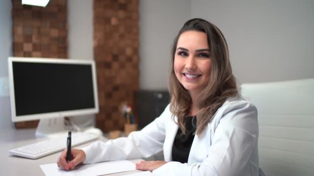 vídeos de stock, filmes e b-roll de doutor fêmea que senta-se na mesa na clínica - dentista